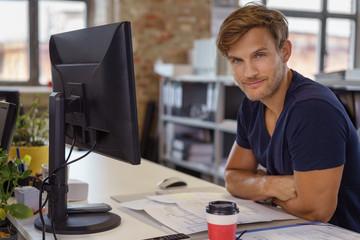 zufriedener junger mitarbeiter arbeitet am computer