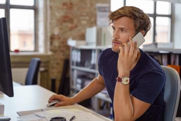 junger geschäftsmann im büro telefoniert und schaut auf pc