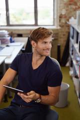 junger mitarbeiter im büro mit tablet