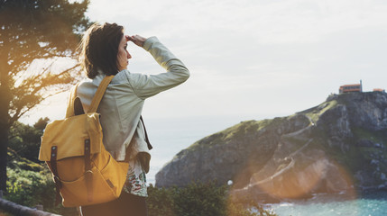Wall Mural - Hipster young girl with backpack enjoying sunset on seascape mountain. Tourist traveler on background valley landscape view mockup. Hiker looking sunlight ocean in trip holiday in basque island