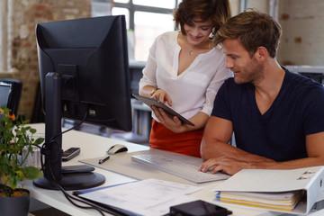 kollegen unterhalten sich im büro und schauen auf ein tablet