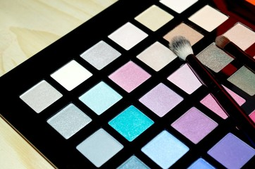 Colorful make up palette with makeup brushes on wooden background