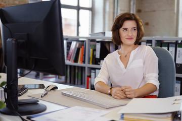 junge angestellte im büro schaut lächelnd zur seite