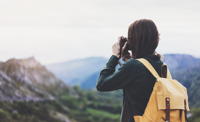 Tourist traveler photographer taking pictures of landscape on vintage photo camera on background valley view mockup sun flare, hipster girl with backpack enjoying sunset on peak of foggy mountain