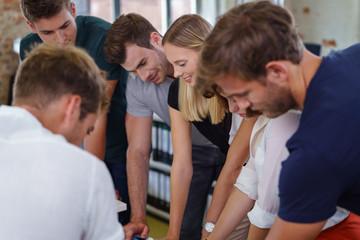 junges team schaut gemeinsam auf unterlagen auf dem schreibtisch