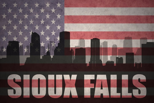 abstract silhouette of the city with text Sioux Falls at the vintage american flag