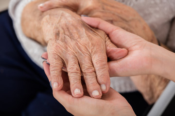 Female Doctor Holding Hand Of Senior Patient