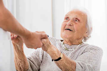 Senior Patient Holding Hands Of Female Doctor
