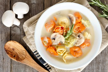 Rainbow tortellini and mushroom soup in a white bowl, above scene on a rustic wood background