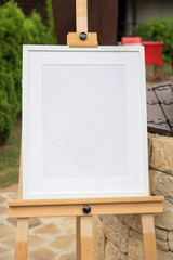 White frame mockup on a wooden stand