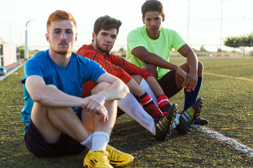 Three football players resting