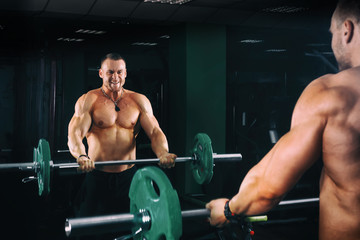 power athletic guy bodybuilder working out biceps with barbell in front of mirrors, in dark gym