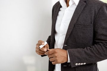 Young successful african businessman standing near board in office.