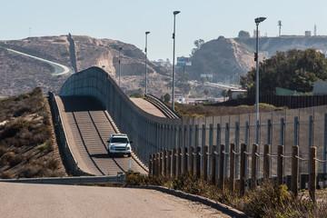 Border Patrol vehicle patrolling along the fence of the international border between San Diego, California and Tijuana, Mexico