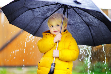 Child with big black umbrella in the rain
