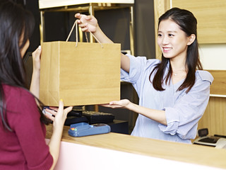 young asian female salesclerk handing merchandise to customer