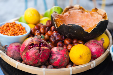 Lemons and pomegranates in a wooden bowl on a tabletop.