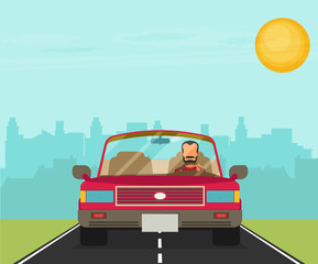 Picture of car on the road with city silhouette on background