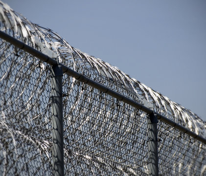 A fence covered in concertina wire surrounding a maximum security prison.