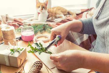 Woman wrapping eco Christmas gifts presents with brown paper, string and natural branches and decor elements on wooden table at home