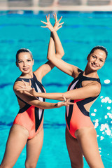Synchronized Swimmers. Standing  by the pool