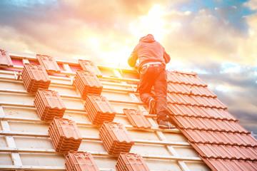 Obraz Dachdecker auf einem Spitzdach  - fototapety do salonu