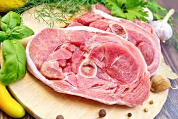 Turkey steak raw with garlic on board