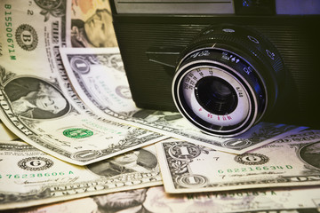 Vintage camera and money - business concept