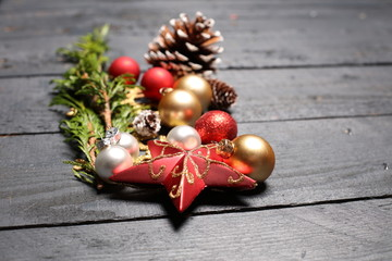 Christmas background. Green Fir tree branches with pine cones, gold snowflakes, ball, stars on wooden background
