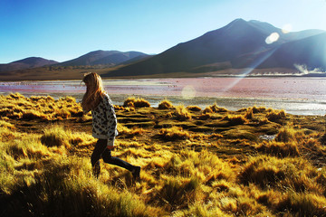 young caucasian blond woman walking at lagoon Colorada, Bolivia