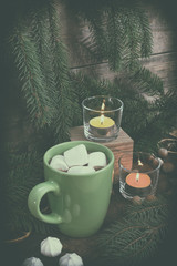 Hot chocolate with marshmallow in green cup and two light candles with Christmas and New Years decor and Christmas tree on dark wooden background