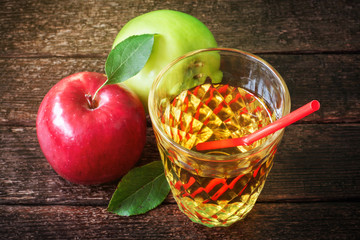 Glass of apple juice with red and green apples on wooden background
