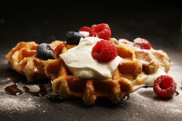 Fresh homemade waffles with ricotta served with whipped cream and berries