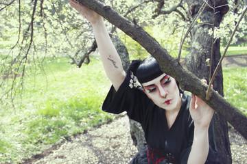 Retrato de una joven disfrazada de geisha en un parque con cerezos en flor