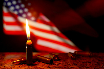 Candles flag tragedy in USA weapons dark background.