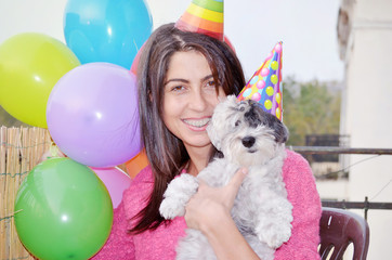 happy young woman celebrating birthday with her dog with balloons and hats