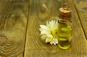 Natural organic flowers oil in handmade bottle and flower are on the wooden table with place for text
