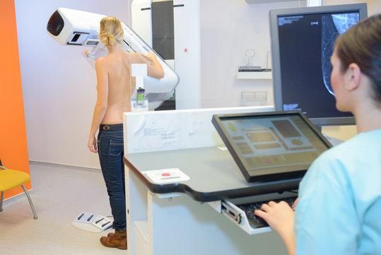 Rear view of woman having mammogram