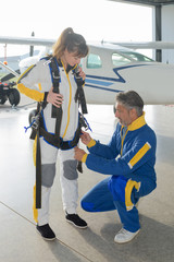 Man fastening straps on parachutist's harness