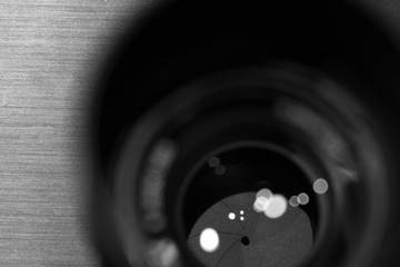 closeup macro of camera lense with reflections low key black and white image with aperture blades