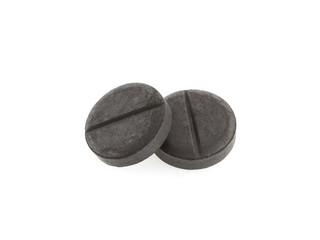 Active black charcoal pills isolated on white background