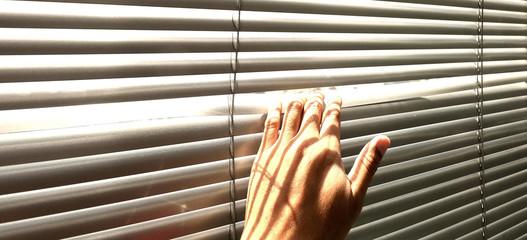 Hand taking a peek through the window blinds