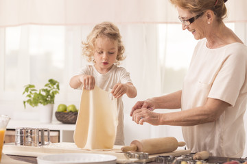 Child making cake with grandmother