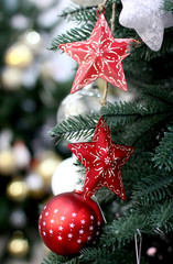 Craft red Christmas tree decorations and Happy New Years decoration hang on green spruce branch
