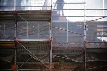 Baustellengerüst  / Die Silhouette und der Schatten eines Bauarbeiters während einer Restauration hinter einem Baugerüst.