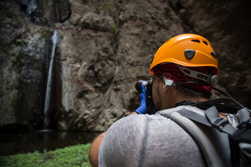 Backpacker man hiking and taking pictures of waterfall in Barranco del Infierno in Tenerife. Canary islands, Spain