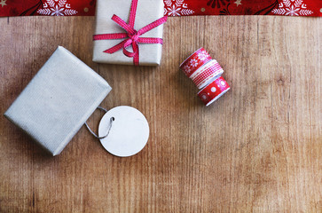 Christmas presents with red tied bow, label and ribbon laid on a wooden table background. Top view and copy space
