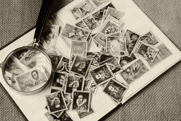 A small selection of old and used, stamps and magnifying glass. Subjects captured against soft window lighting on rustic fabric background. Overhead view.
