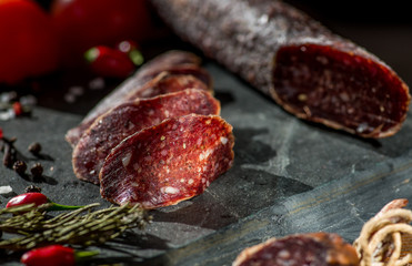 thin sliced sausage jerked on a stone background