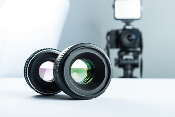 Two lenses on a white table against the background of the camera to light and softbox.